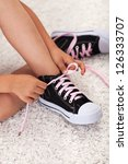 Child hands tie shoelaces - closeup - stock photo