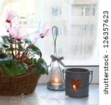 Pink cyclamen next to candlesticks on a window in winter. - stock photo