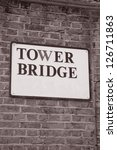 Tower Bridge Sign in London, England, UK on Brick Wall in Black and White Sepia Tone - stock photo