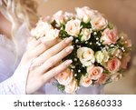 Bride hand with bridal bouquet of roses. - stock photo
