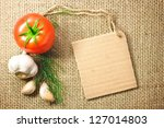 Photo of tomato and garlic vegetables and price tag on sacking background texture - stock photo