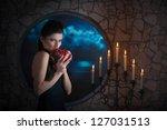 Fantasy style portrait of demonic woman biting a pomegranate - stock photo