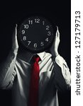 Time management with businessman holding clock in front of his head. - stock photo