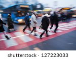 commuters crossing the street at a bus station - stock photo