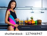 Young pregnant asian woman on kitchen. - stock photo