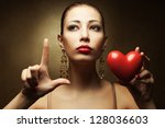 """Portrait of a fashionable model with sexy red lips holding red heart (love symbol) and showing """"L"""" (love symbol) with her hand over golden background. Close up. Studio shot - stock photo"""