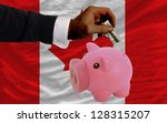 Man putting dollar into piggy rich bank national flag of canada in foreign currency because of inflation - stock photo