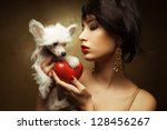 Portrait of two friends:  fashionable model with sexy red lips holding red heart (love symbol) and white little chinese crested dog. Both posing over golden background. Profile. Close up. - stock photo