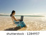Asian woman with laptop working at the beach - stock photo