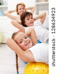 Kids exercising with their mother using gymnastic balls - stock photo