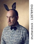 Portrait of a handsome glamorous bald bunny-man posing over golden background. copy-space. studio shot - stock photo
