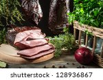 Closeup of freshly smoked ham in a rural pantry - stock photo