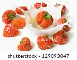 Red strawberry fruits falling into the milky splash - stock photo