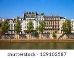 Famous quay of river Seine in Paris with buildings and trees. - stock photo