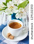 Cup of coffee with brown sugar and white flowers. - stock photo