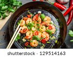 Closeup of shrimps on pan with fresh herbs - stock photo