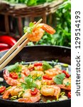 Closeup of fried shrimp on chopsticks with herbs - stock photo