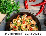 Closeup of shrimps fried on pan and fresh herbs - stock photo