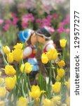 Two kissing dolls in tulip garden. - stock photo