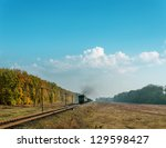 train with smoke over it under cloudy sky - stock photo