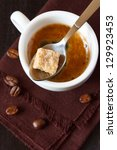 Cup of coffee with cube of brown sugar in a spoon close-up. - stock photo