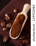 Fresh ground coffee in a wooden scoop and coffee beans on a brown background. - stock photo