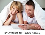 Happy couple lying in bed with digital tablet - stock photo