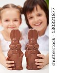 Happy easter kids smiling and holding large chocolate bunnies - closeup - stock photo