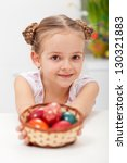 Little girl with basket full of easter eggs - closeup - stock photo