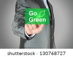 Businessman pushes touch screen go green button. Eco concept. - stock photo