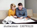 Happy young couple analyzing home blueprints. - stock photo