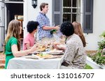 Man pops champagne with group of friends having a gathering party, sitting around a table with plenty of food - stock photo