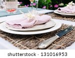 Close up of simple rustic outdoor entertaining table setting with neutral nude colour scheme - stock photo