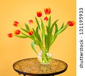 Red tulips flowers  in a vase on mosaic table. - stock photo