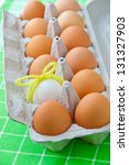 One white egg  in a carton package of brown eggs. selective focus - stock photo