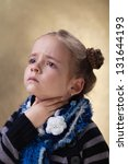 Little girl with sore throat in flu season touching her neck - stock photo