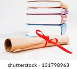 Diploma with red ribbon and books - stock photo