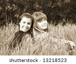 two girls sitting in grass - stock photo