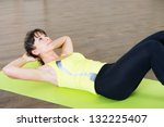 Pretty young girl fitness workout on mat in gym - stock photo
