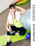 Fitness woman relax with water bottle and exercise ball - stock photo