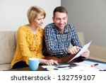 Happy couple calculating bills sitting sonf sofa in living room - stock photo