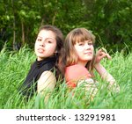 two girls sitting in green grass - stock photo