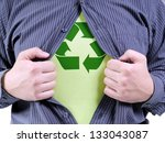A man wearing shirt transforming into Eco superhero with green recycle arrow symbol underneath on chest - recycle concept - stock photo
