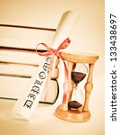 Diploma and books and hourglass - stock photo