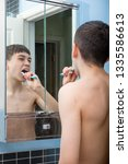 Teenage caucasian boy cleaning his teeth in the morning - stock photo