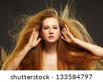 portrait of young beautiful red-haired woman touching her hair on gray - stock photo