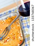 Eggplant Casserole food dish and a glass of wine - stock photo