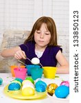 Young girl in the process of coloring Easter Eggs - Step two, the egg on a spoon about to be lowered into the cup of dye - stock photo