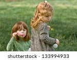 Two young Caucasian girls blowing bubbles - stock photo