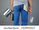 Closeup of a male painter seen from behind while he carries two paint cans and a roller. Man is unrecognizable, torso and legs only. Horizontal format. - stock photo